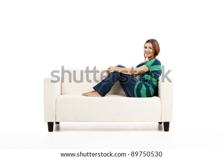Beautiful woman relaxing on a white sofa with a cup of coffee - stock photo