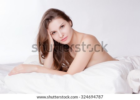 Beautiful woman relaxing on bed, bedtime in morning - stock photo