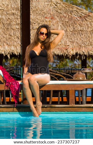 Beautiful woman relaxing on lounger in hotel, bali - stock photo