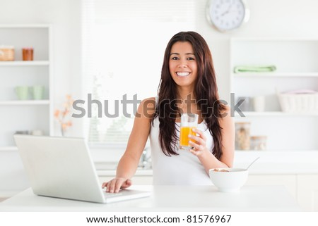 Beautiful woman relaxing with her laptop while holding a glass of orange juice in the kitchen - stock photo