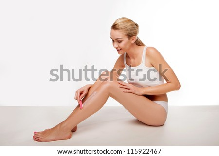 Beautiful woman removing her leg hair using a depilatory cream and applicator seated on the floor - stock photo