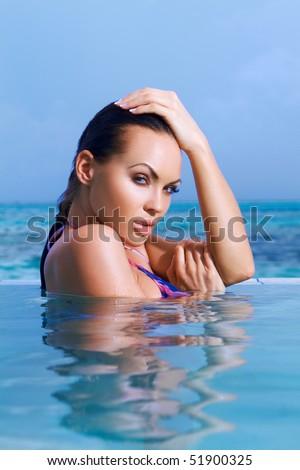 Beautiful woman resting in pool at Maldives - stock photo