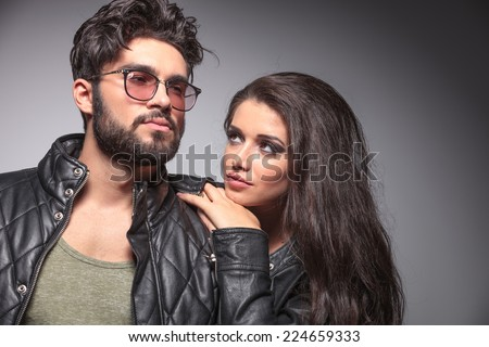Beautiful woman resting on her lover shoulder looking at him, while he is looking away. - stock photo