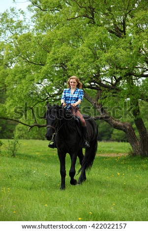 Beautiful woman riding horse in forest - stock photo