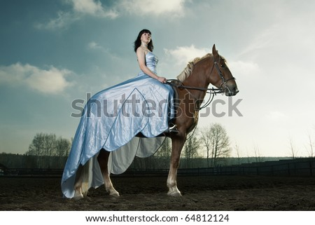 Beautiful woman riding on a brown horse - stock photo