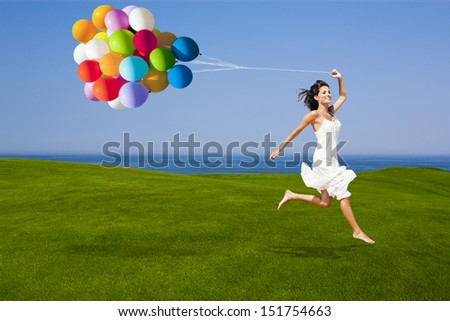 Beautiful woman running and jumping on a green meadow with a colored ballons - stock photo