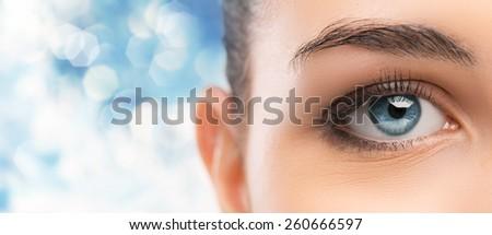 Beautiful woman's blue eye close up looking at camera - stock photo