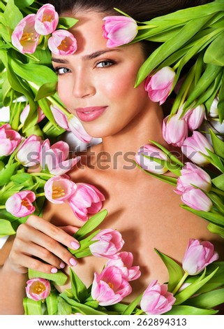 Beautiful woman's face surrounded by pink tulips. Spring Flower. Springtime. Perfect skin - stock photo