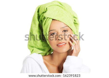 Beautiful woman's face with a cream under eye. Isolated on white.  - stock photo
