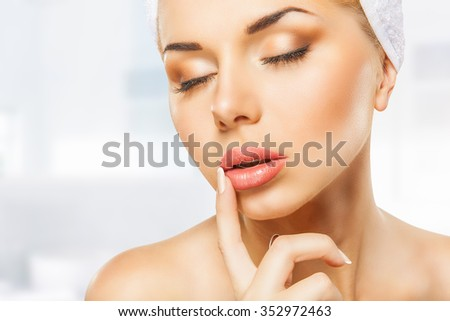 Beautiful woman's face with closed eyes on a light background - stock photo