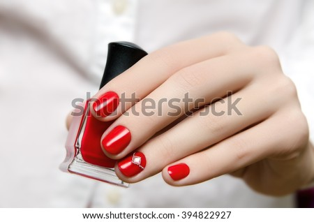 Beautiful woman's hand with red nail design holding a nail polish bottle. - stock photo
