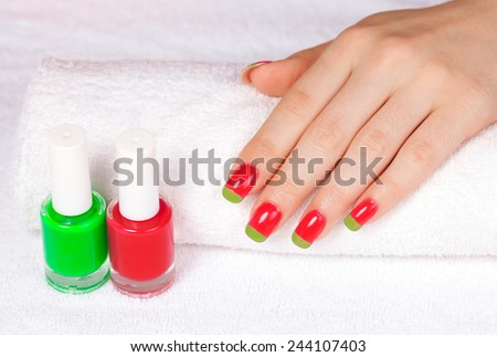 Beautiful woman's hand with two-color manicure on white towel - stock photo