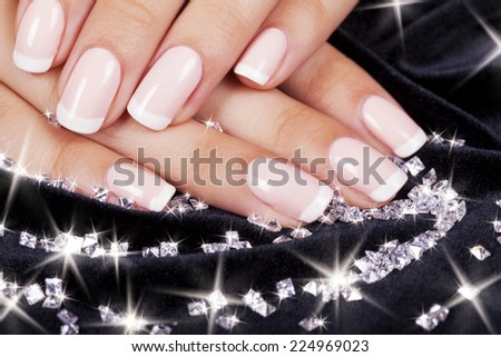 Beautiful woman's nails with french manicure and diamonds. - stock photo
