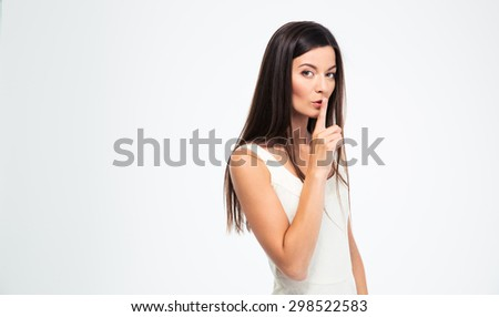 Beautiful woman showing finger over lips isolated on a white background. Be quiet!!! - stock photo