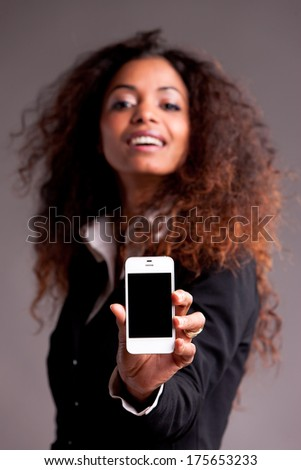 Beautiful  woman showing her mobile smartphone - stock photo