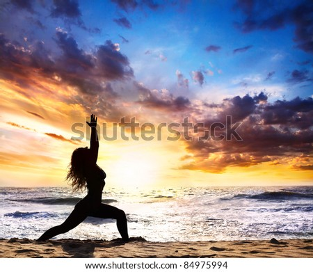 Beautiful Woman silhouette doing virabhadrasana I warrior pose on the sand beach and ocean nearby at sunset background in India, Goa - stock photo