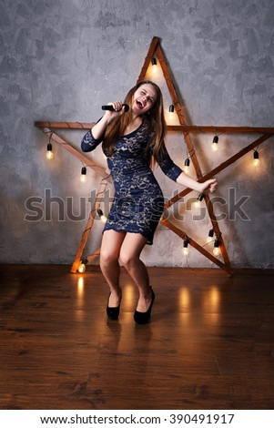 beautiful woman singing on stage with a microphone in his hands - stock photo