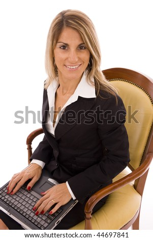 Beautiful woman sit on an armchair typing on a laptop - stock photo