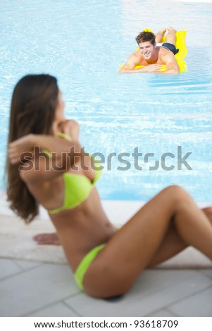 Beautiful woman sitting by pool, man on air mattress - stock photo