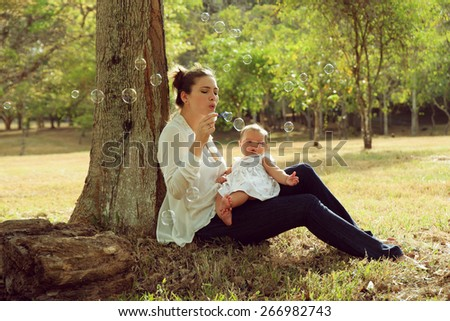 Beautiful woman sitting down tree in park and leaning on trunk with her little baby on legs, playing with her daughter blowing soap bubbles and smiling. Wide shot at sunset - stock photo
