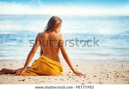 beautiful woman sitting from the back on beach, bali - stock photo