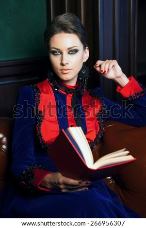 beautiful woman sitting in a leather chair in retro dress reading a book - stock photo