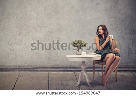 beautiful woman sitting in a living room drinking tea - stock photo