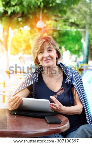 Beautiful  woman sitting in a sidewalk cafe holding a digital tablet and looking away. - stock photo