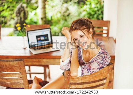 beautiful woman sitting near computer at home - stock photo