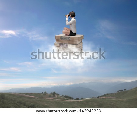beautiful woman sitting on a pile of old books in the clouds watching with binoculars - stock photo