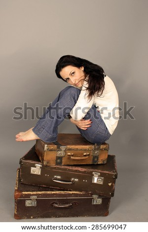 Beautiful woman sitting on a suitcase on a gray background. She hugged her knees, her feet bare. Girl sad and lonely. - stock photo