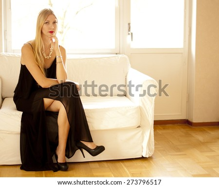 Beautiful woman sitting on couch - stock photo