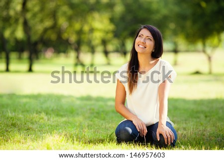 Beautiful woman sitting on grass in park, she is looking sideways - stock photo