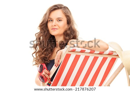 Beautiful woman sitting on sun lounger and holding sunglasses isolated on white background - stock photo