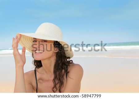 Beautiful woman sitting on the beach with straw hat - stock photo