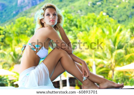 Beautiful woman sitting on the edge of swimming pool - stock photo