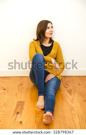 Beautiful woman sitting on the floor with a thinking expression - stock photo