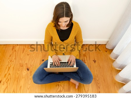 Beautiful woman sitting on the floor working on the laptop - stock photo
