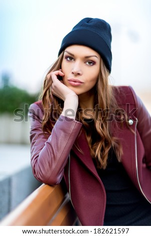 Beautiful woman sitting outdoors on a park bench in the fall - stock photo