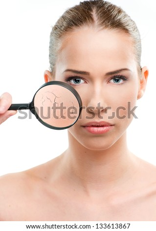 Beautiful woman, skin close up with a magnifying glass, over a white background - stock photo