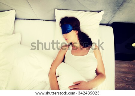 Beautiful woman sleeping in bed with eyes band. - stock photo