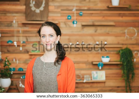 Beautiful woman, small business shop owner looking at camera in her shop - stock photo