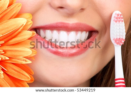 Beautiful woman smile, teeth and a fresh flower - stock photo