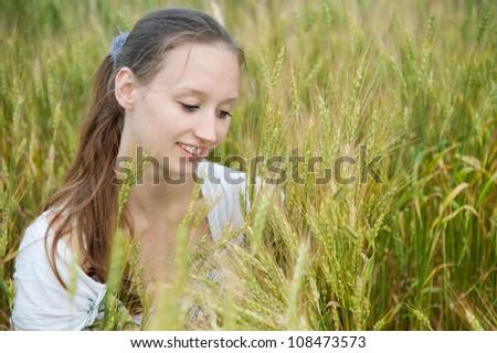 Beautiful woman smiles in the wheat field - stock photo