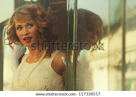 Beautiful woman smiling as she steps from train carriage - stock photo