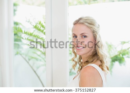 Beautiful woman smiling at camera in the bathroom - stock photo