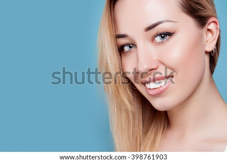 Beautiful woman smiling. portrait of attractive caucasian smiling woman blond on blue studio shot, studio shot - stock photo