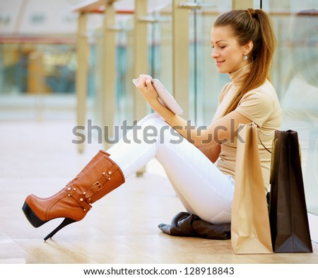 Beautiful woman smiling with her digital tablet and shopping bags - stock photo