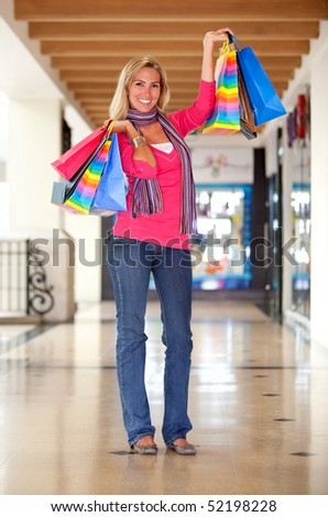 Beautiful woman smiling with shopping bags in a mall - stock photo
