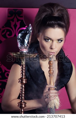 Beautiful woman smoking hookah in nightclub - stock photo